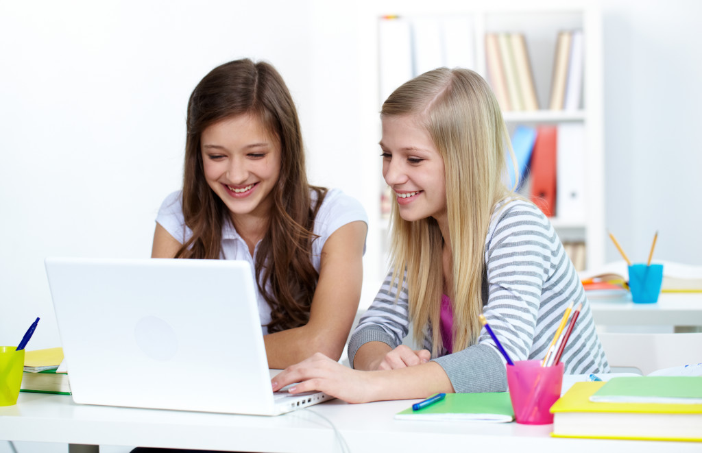 Girls working on a laptop in college